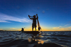Asian fisherman on wooden boat casting a net for catching Stock Image