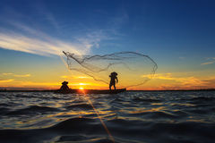 Asian fisherman on wooden boat casting Royalty Free Stock Photography