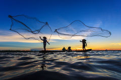 Asian fisherman on wooden boat casting a net for catching Stock Photo