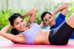 Asian fitness couple doing sit-up in tropical home. Asian fitness couple, men and woman, doing sit-up in tropical home royalty free stock photos