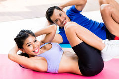 Asian fitness couple doing sit-up in tropical home Stock Photography
