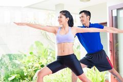 Asian fitness couple at sport workout in tropical home royalty free stock image