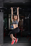 Asian fitness girl with perfect shape body making elevations pull up in gym. Royalty Free Stock Photos