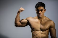 Asian Fitness Model Flexes Bicep Muscle. An Asian fitness model flexing his bicep muscle. Front facing Stock Photo