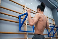 Asian Fitness Model Perform Pull Up Workout. NnShowing off muscle on the back Royalty Free Stock Photography
