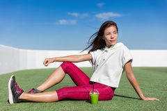 Healthy fit Asian athlete fitness model woman. Asian fitness model in summer outdoors sitting on outdoor grass gym drinking a healthy green smoothie juice detox royalty free stock photography