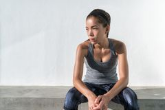 Asian fitness runner woman thinking during workout. Asian fitness runner woman thinking pensive during workout. Serious athlete model on gym break tired feeling royalty free stock image