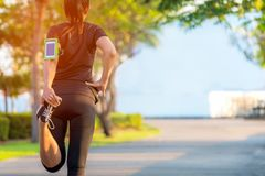 Asian fitness woman runner stretching legs before run outdoor workout in the park. stock photos