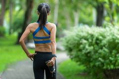 Asian fitness woman runner stretching legs before run outdoor workout in the park. Royalty Free Stock Photos