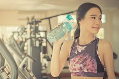 Asian fitness woman wearing purple cloth is drinking fresh water in fitness. Asian fitness woman wearing purple cloth is drinking healthy fresh water in fitness Royalty Free Stock Image