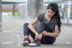 Asian fitness young woman Running injury leg accident of workout exercising on street in urban city . sport runner girl sitting. On floor sprained ankle in pain royalty free stock photo