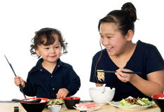 Asian food. Two asian children eat asian food,isolated on a white background stock images