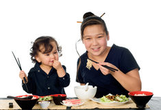 Asian food. Two asian children eat asian food, isolated on a white background royalty free stock image