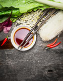 Asian food background with soy sauce, chopsticks, rice noodles and vegetables for tasty Chinese or Thai cooking,. Top view royalty free stock photography