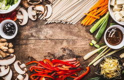 Asian food background with vegetarian cooking ingredients and chopsticks : tofu, noodles, ginger, lemongrass, cut vegetables, Spro Royalty Free Stock Photo