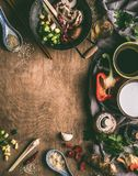 Asian food background with wok , coconut milk, soy sauce, sesame oil, chopped spices and vegetables on rustic wooden background. Royalty Free Stock Photography