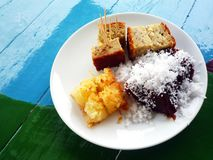Asian food - cakes and dessert. An assortment of ethnic asian snacks, cakes for dessert, kuehs made from wheat flour and grated coconut, palm sugar, banana, etc Stock Photos