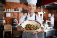 Asian Food Chef Presenting Dish. Portrait of proud professional chef presenting Asian food dish, focus on foreground stock photos