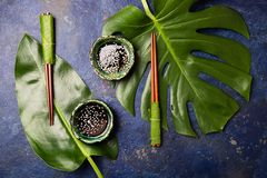 Asian food concept. Chopstick and soysauce soy sauce with white sesame on blue background with tropical leaves . Top. View stock photography