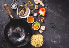 Asian food cooking concept. Dark background. Empty wok pan, noodles, vegetables stir fry, shrimps, chopsticks. Space for text. Asian/Chinese food. Top view stock photography
