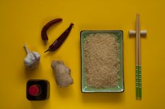 Asian food ingredients, spices and sauces on a sunny yellow background, top view, copy space. Asian food ingredients, spices and sauces on a sunny yellow stock image