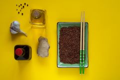 Asian food ingredients, spices and sauces on a yellow background. The concept of the most popular Chinese dishes in the world. Some types of Asian cuisine, top stock image