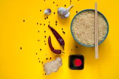 Asian food ingredients, spices and sauces on a yellow background. The concept of the most popular Chinese dishes, copy space. Asian food ingredients, spices and royalty free stock photos