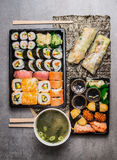 Asian food menu set with sushi, fresh summer rolls and miso soup on Nori and gray stone background royalty free stock image