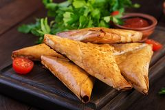 Asian food. Samsa samosas with chicken fillet and cheese. On wooden background royalty free stock image