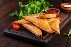 Asian food. Samsa samosas with chicken fillet and cheese. On wooden background royalty free stock photos