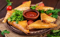 Asian food. Samsa samosas with chicken fillet and cheese. On wooden background royalty free stock photo