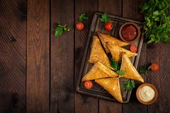 Asian food. Samsa samosas with chicken fillet and cheese. On wooden background. Top view stock images