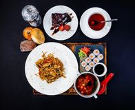 Asian food set. Fried noodles with chicken, miso soup, sushi with salmon, cup of tea and cake. stock photos