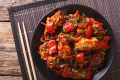 Asian food: spicy pork in sweet and sour sauce close-up. Horizon Stock Image