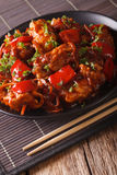 Asian food: spicy pork in sweet and sour sauce close-up. vertica Stock Images