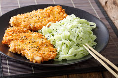 Asian food: steak in breaded Panko and green noodles with sesame Royalty Free Stock Photos