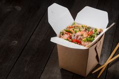 Asian food to go. Opened box of rice with seafood and vegetables, prepared in wok, and chopsticks on wooden table. Space in the left to insert your text royalty free stock image