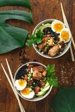 Asian food Two poke bowl fried rice chicken fillet eggs top view stock photography