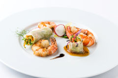 Asian food on white plate. Prepared shrimps, spring rolls and salad on white plate Royalty Free Stock Image