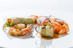 Asian food on white plate. Prepared shrimps, spring rolls and salad on white plate Royalty Free Stock Photography
