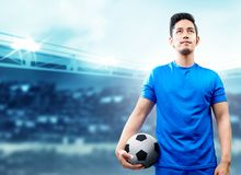 Asian football player man in blue jersey holding the ball on the football field stock photos