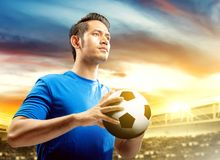 Asian football player man in blue jersey holding the ball on the football field royalty free stock photography