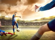 Asian football player man sliding tackle the ball from his opponent before him kicking the ball to the goal stock images