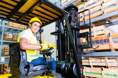 Asian fork lift truck driver lifting pallet in storage Stock Image