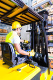 Asian fork lift truck driver lifting pallet in storage. Warehouse Stock Image