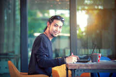 Asian freelance man working on computer laptop toothy smiling fa Royalty Free Stock Photography