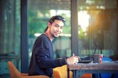Asian freelance man working on computer laptop toothy smiling fa. Asian freelance man working  on computer laptop toothy smiling face Royalty Free Stock Photography