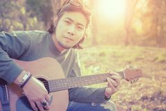 Asian freelance musician playing folk guitar outdoor against bea Stock Photo