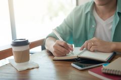 Asian man writing text on notebook Stock Image