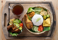 Asian fried chicken meal set. Famous traditional Indonesian food. Delicious nasi ayam penyet with sambal belacan. Fried chicken rice and tea with overhead view stock images